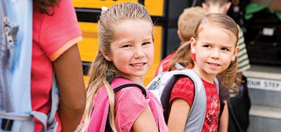 school girls getting on bus