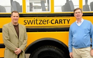 Jim Switzer and Doug Carter next to a school bus