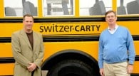 Jim Switzer and Doug Carter next to a school bus